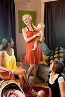Young mother holding baby and laughing with friends