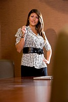 Portrait of businesswoman standing in office with laptop on table