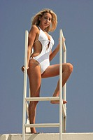 Portrait of young woman in bikini standing on metal ladder