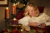 Mature woman lying on couch and listening to ipod