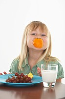 Girl having snack and holding orange in her mouth