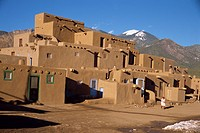 Woman sweeping up, in front of the adobe buildings of the north complex, dating from 1450, Taos Pueblo, UNESCO World Heritage Site, New Mexico, United...
