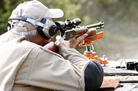 a man target shooting with a high powered rifle