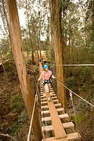 Hawaii, Maui, Zipline Adventure, Woman walking across a wooden bridge.