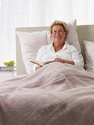 elderly lady reading in bed