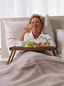 senior lady having breakfast in bed
