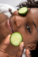 A young black girl using slices of cucumber to enhance her skin. Cucumbers are a strong source of vitamin C, vitamin K, potassium, vitamin A, vitamin ...