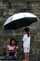 Woman and child with umbrella during the visit of the Borobudur temple Java Indonesia