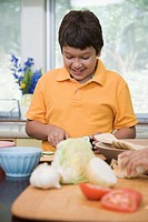 Boy cutting vegetables in kitchen