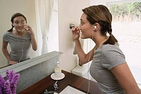 Woman using eyelash curler in mirror