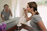 Woman using eyelash curler in mirror