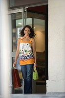 Young woman leaving store with shopping bags, smiling at camera