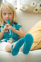 Little girl sitting on sofa, playing recorder
