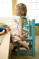 Toddler girl sitting at table, touching ankle, side view