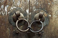 Old wooden doors, close-up of iron door handles linked by padlock