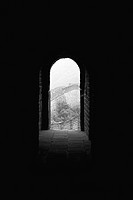 Looking down dark passageway to open arched doorway of room perched atop Great Wall of China