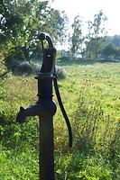 Old-fashioned water pump in sunny meadow
