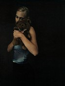 Woman standing in dark and hugging teddy bear, eyes closed