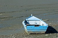 Rowboat stranded on mud flat