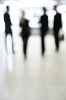 Business people standing in lobby, full length, defocused