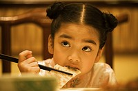 Girl eating with chopsticks, looking up, head and shoulders