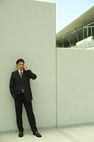 Buisnessman holding cell phone to ear, leaning against wall, full length