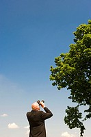 Man looking through binoculars up tree