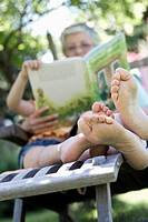grandmother sitting in garden reading from book to little girl