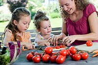 mother showing her two daughters how to make salad of tomatoes