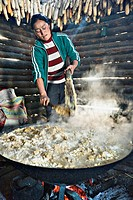 Woman stirs the corn whiskey mash over open fire in log cabin, Tong Dang, Yunnan, China high ISO, grain, blurred motion No model release available