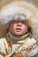 Tibetan girl peers out from beneath her big fur hat, Daocheng, Sichuan, China No model release available