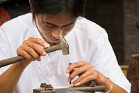 Male silversmith tools a design into a piece, Dali, Yunnan, China No releases available
