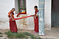 Young Mongolian Buddhist monk helps his fellow monk wind up his robe for a ceremony, Erdene Zuu monastery, north central Mongolia No releases availabl...