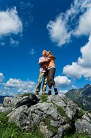 mature couple standing on rock in the mountains embracing each other