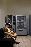 King Henry VIII sleeping on sofa near vending machine