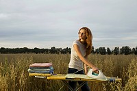 Young Woman Ironing in a Field