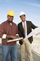 Surveyor and construction worker with blueprints portrait