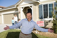Portrait of mid_adult man in front of new house