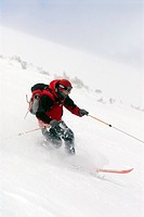 Man telemark skiing through powder on North Diamond Peak in Cameron Pass, Colorado