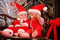 Two infant girls wearing Chrismas outfits sitting in wooden chair with Christmas decorations in background winter Alaska