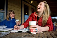 Two young women laugh while drinking tea at Two Sisters Bakery in Homer, Alaska