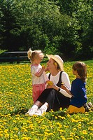 Mother & Daughters picking dandelions in a park USA