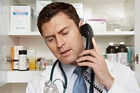 Male doctor using phone in hospital