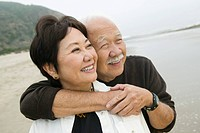 Senior couple embracing on beach (thumbnail)