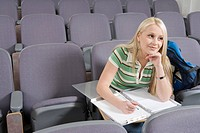 Female student writing in lecture hall (thumbnail)
