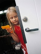 Flicka Med Vattenpistol, Girl 7_8 Showing Toy Gun Against Door