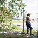 Kvinna 35 År Med Gummistövlar Rensar Fisknät I Stockholms Skärgård, Sverige, Woman Cleaning Fishing Net