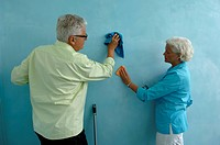 Senior man and woman both cleaning the wall with cloth