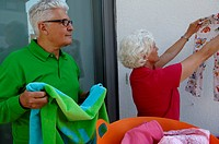 Senior couple hanging out the laundry (thumbnail)