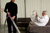 Woman is vacuum_cleaning while her husband is reading newspaper
